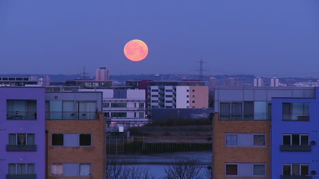 ws t/l view of moon setting over city residential landscape with advent of dawn / london, united kingdom  - district stock videos & royalty-free footage