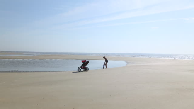 ws view of mother and baby boy playing in water on beach / st simon's island, georgia, united states - sportkinderwagen stock-videos und b-roll-filmmaterial
