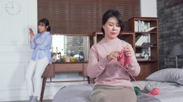 View of Mother Knitting on the Bed and Daughter Watching at Smartphone on the Desk