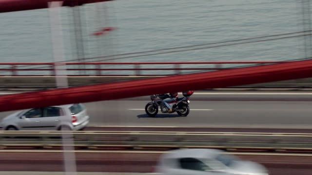 "ws aerial ts zi zo view of motorbike crossing ""ponte 25 de abril"" / lisbon, portugal   - bridge built structure stock videos & royalty-free footage"