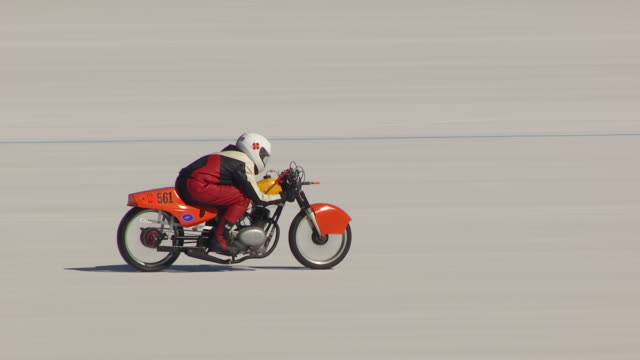 cu aerial zo ts view of motorcycle driving on race track and bonneville salt flats with cars driving in during speed week / utah, united states - bonneville salt flats stock videos and b-roll footage