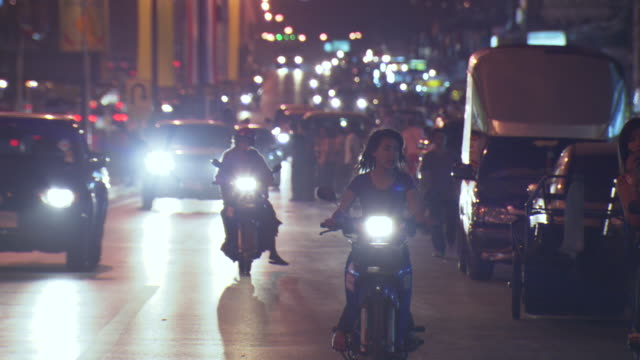WS View of Motorcycles, scooters, cars and pedestrians navigate Mae Sai main street at night / Mae Sai, Chiang Rai, Thailand