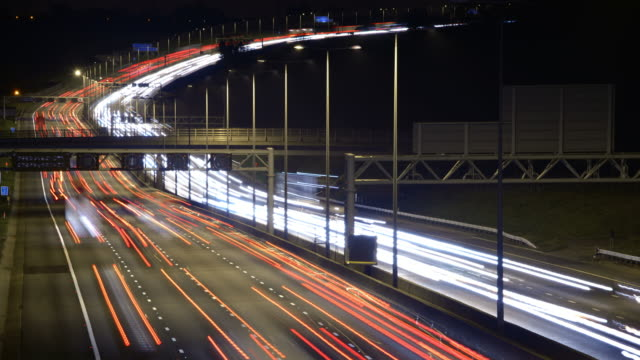 ws t/l view of motorway with heavy traffic on slope across six lanes overhead signs view from motorway bridge at night  / redbourn, bedfordshire, united kingdom - tail light stock videos & royalty-free footage