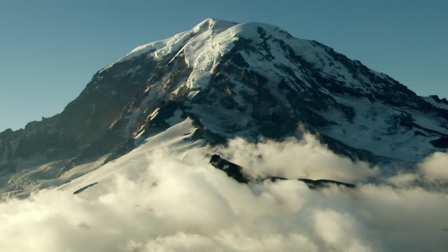 ws aerial view of mount rainier summit surrounded by clouds / washington, united states - mt rainier stock videos & royalty-free footage