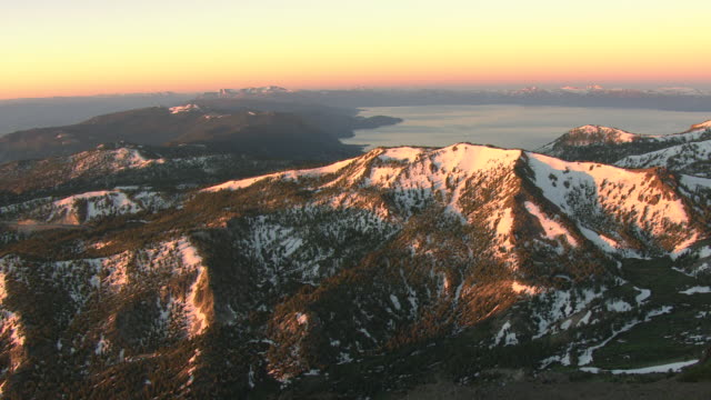 ws aerial view of mount rose summit to lake tahoe in sierra nevada with snowy peaks and morning pink haze in sky / nevada, united states - カリフォルニアシエラネバダ点の映像素材/bロール