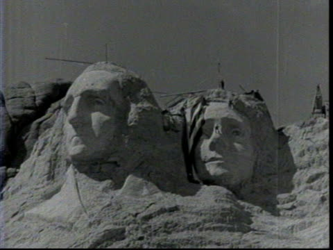 view of mount rushmore during construction / workers on heads removing american flag to reveal thomas jefferson / detail of george washington /... - thomas jefferson stock videos & royalty-free footage