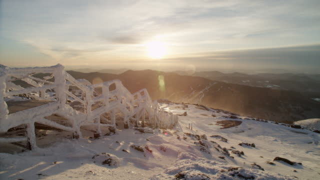 """ws pan view of mount washington observatory, snow covered bridge with mountains, strong winds, sunrise / north conway, new hampshire, united states"" - new hampshire stock-videos und b-roll-filmmaterial"
