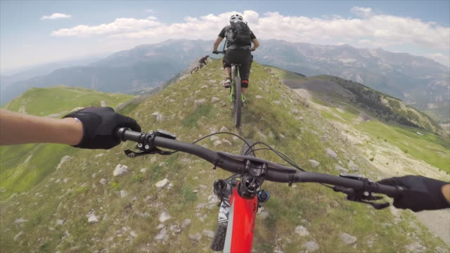 pov view of mountain biking handlebars on bicycles, men riding bikes in switzerland. - wearable kamera stock-videos und b-roll-filmmaterial