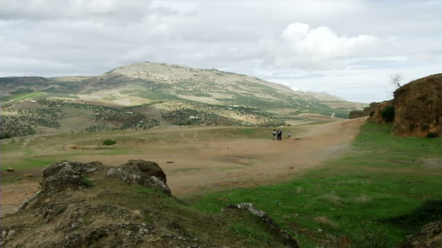 WS View of mountain countryside outside and children playing together / Fez, Fes-Boulemane, Morocco
