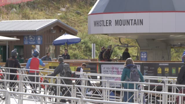 view of mountain cyclists at entrance to ski lifts near whistler village gondola, whistler, british columbia, canada, north america - western script stock videos & royalty-free footage