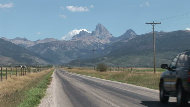 view of mountain road in grand teton united states - grand teton stock videos & royalty-free footage