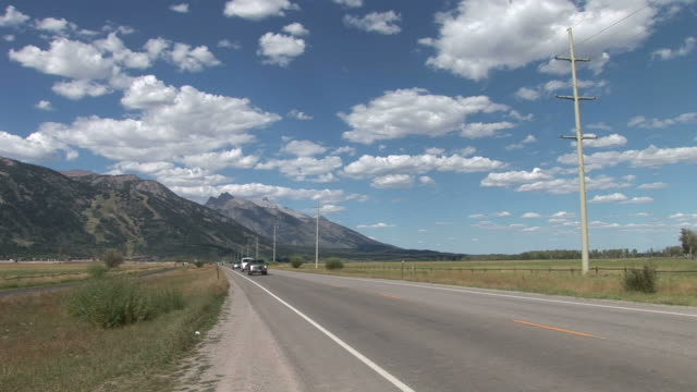 view of mountain road in grand teton united states - grand teton stock-videos und b-roll-filmmaterial