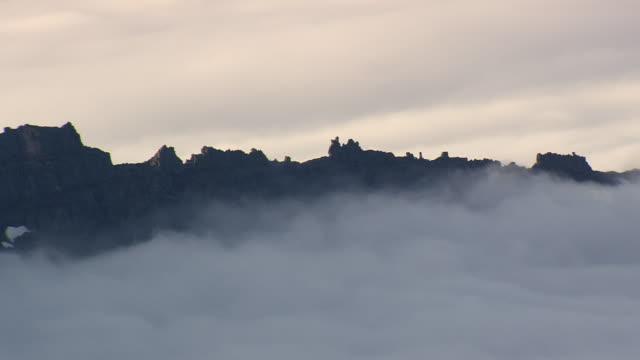 vídeos de stock, filmes e b-roll de ws areail view of mountain top with fog / iceland - islândia