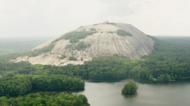 ws aerial pov view of mountain with tree are and river / stone mountain, georgia, united states - quarz stock-videos und b-roll-filmmaterial