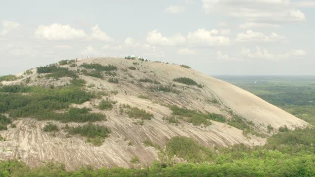 ws tu aerial pov view of mountain with tree area / stone mountain, georgia, united states - quarz stock-videos und b-roll-filmmaterial