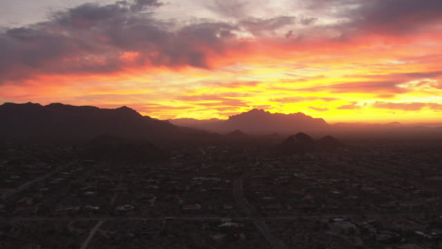 WS AERIAL View of mountains against fiery sky at sunrise and buildings in valley / Phoenix, Arizona, United States