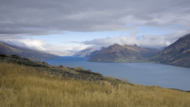 WS T/L View of mountains and lake with cloudy sky / Lake Wakatipu, South Island, New Zealand