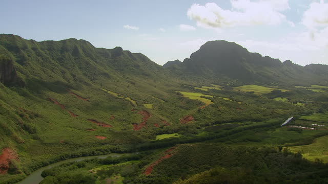 vídeos de stock, filmes e b-roll de ws aerial view of mountains covering in greenery on island of kauai / hawaii, united states - vale