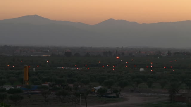 ws view of mountains with cars driving by very far away around dusk / marrakech, tensift, morocco  - wiese stock videos & royalty-free footage