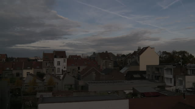 ws t/l view of moving clouds over roof tops of houses / brussels, brussels capital region, belgium - ベルギー点の映像素材/bロール