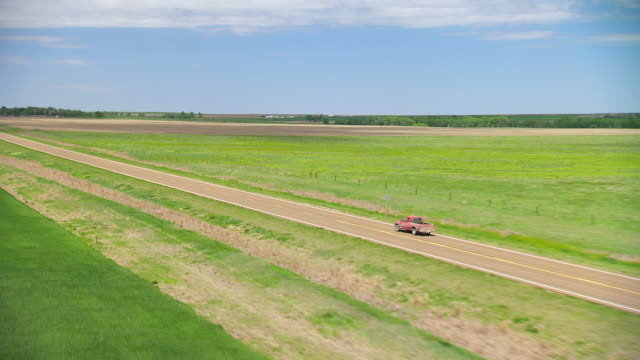 vídeos de stock e filmes b-roll de ws aerial zi ts view of muddy red pickup truck moving on country highway through flat landscape in trego county / kansas, united states - kansas