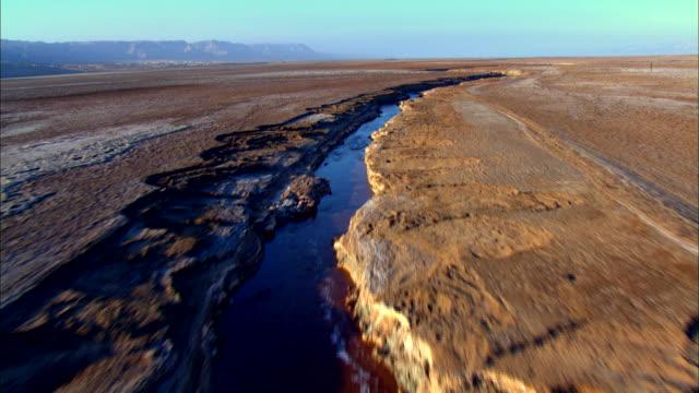 ws aerial pov view of muddy surface of  dead sea / sourn judea desert, israel  - 聖地パレスチナ点の映像素材/bロール
