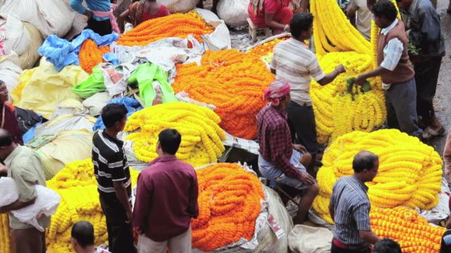 stockvideo's en b-roll-footage met ms ha view of mullikghat flower market with sellers strands of fresh orange and yellow marigold flowers / calcutta, india - guirlande