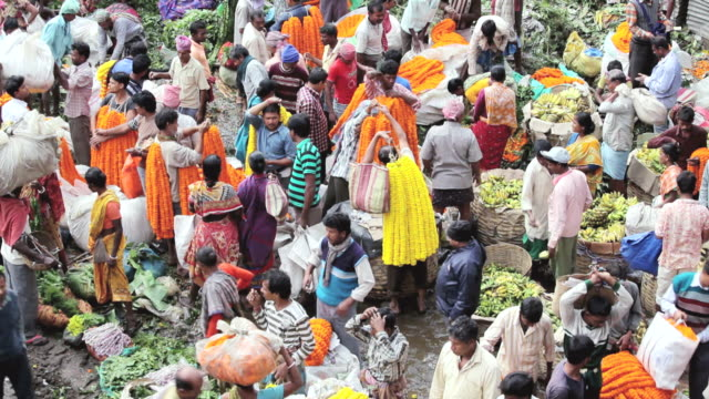 WS HA View of Mullikghat Flower Market with sellers strands of fresh orange and yellow marigold flowers / Calcutta, India