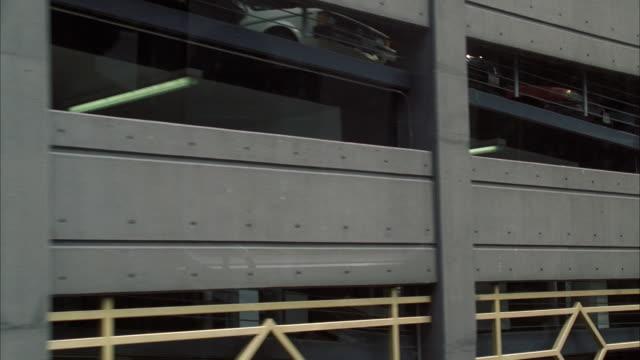 vídeos de stock, filmes e b-roll de ms pan view of multi storey car park through elevated train / chicago, illinois, usa - metrô de chicago