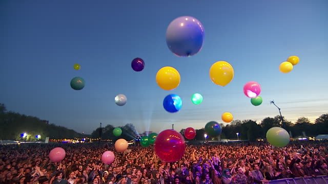 ws pov view of multi-colour balloons in air looking down on festival crowd hitting them up into air / victoria park, london, united kingdom - multicolore video stock e b–roll