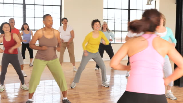 ms pan view of multi-ethnic group of seniors doing aerobic exercise/ richmond, virginia, united states - aerobics stock videos & royalty-free footage