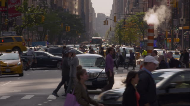 View of multiple New York City Streets with criss-crossing traffic. Steam rises from an orange cone.