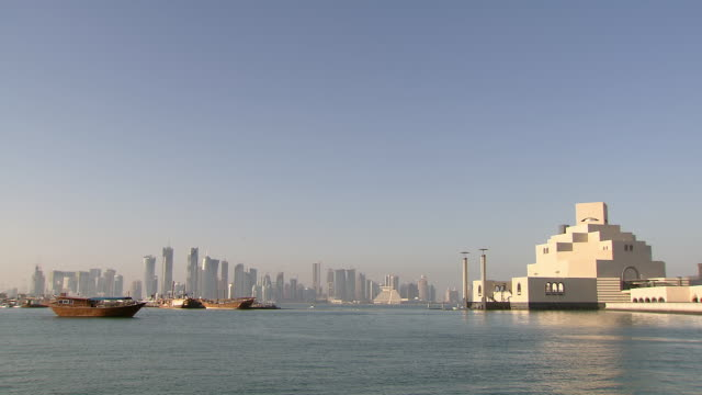ws view of museum of islamic art, modern buildings in doha and boats floating on the sea / doha, qatar  - doha bildbanksvideor och videomaterial från bakom kulisserna