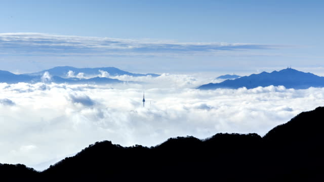 view of n seoul tower and cloud sea from mountain peak(insubong) at mt. bukhansan - peak tower stock videos and b-roll footage