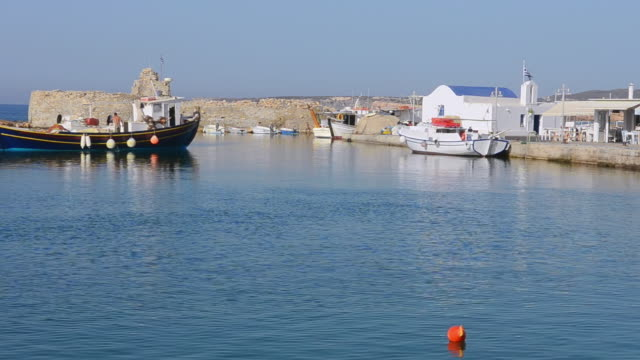 vídeos de stock e filmes b-roll de ws view of naouusa fishing boat moving in port in city center / paros, greece - greece