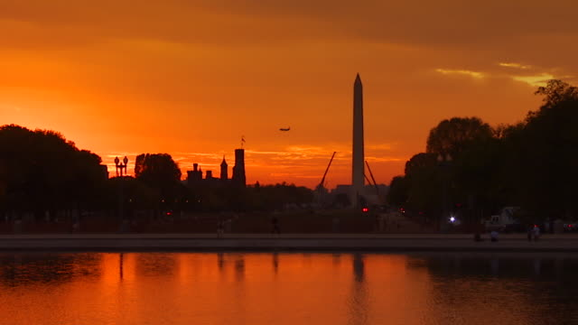 WS View of National Mall during sunset seen from Eastern end with Capitol reflecting pool in foreground and Washington Monument and silhouette as plane crosses sky as it approaches Washington DC / Washington, District of Columbia, United States