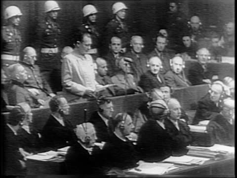 view of nazi prisoners in courtroom including hermann goering and rudolph hess / montage of views of officials in courtroom listening through... - processi di norimberga video stock e b–roll