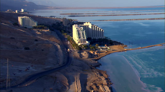 ws aerial pov view of neve zohar and hotels in city / ein boqeq, sourn judea desert, israel  - neve stock videos & royalty-free footage