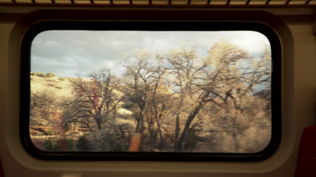 view of new mexico landscape from train car window, pov - treno video stock e b–roll