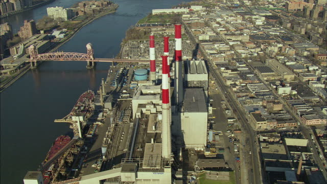 ws pov aerial view of new york city power plant and cargo ships docked at water's edge / new york city, new york, usa - equipment stock videos & royalty-free footage