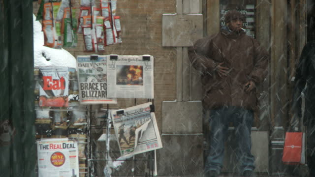 vidéos et rushes de ws view of newsstand with man trying to light cigarette / new york city, new york, usa  - kiosque à journaux