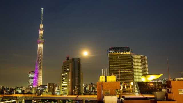 WS T/L View of night scene of moonrise nearby Tokyo sky tree communication tower / Tokyo, Japan