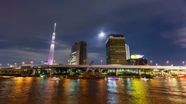 WS T/L View of night scene of moonrise nearby Tokyo sky tree communication tower and sumida river with Asakusa area / Tokyo, Japan