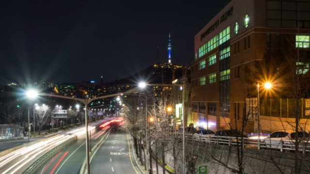 WS T/L POV View of Nightscape and Traffic moving at near the N Seoul Tower(a communication and observation tower located on Namsan Mountain in central Seoul, South Korea) / Seoul, South Korea