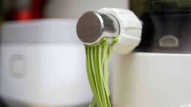 view of noodle machine making spinach noodles - rolling pin stock videos & royalty-free footage