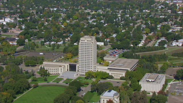 WS ZO AERIAL POV View of North Dakota State Capitol with cityscape / Bismarck, North Dakota, United States