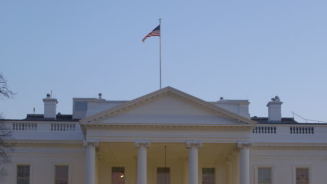 ws tu view of north portico to american flag on top of the white house during sunset / washington, district of columbia, united states - ペディメント点の映像素材/bロール