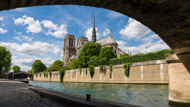 view of notre dame cathedral from under pont de l'archeveche - notre dame de paris stock videos and b-roll footage