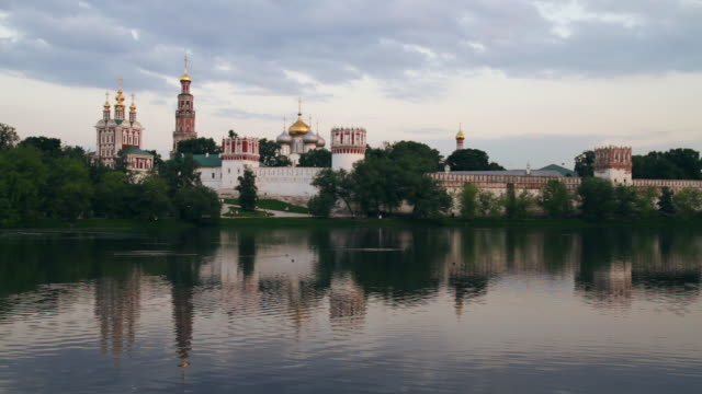 ws view of novodevichy convent in moscow reflecting in pond on against sunset sky / moscow, russia - convent stock videos & royalty-free footage