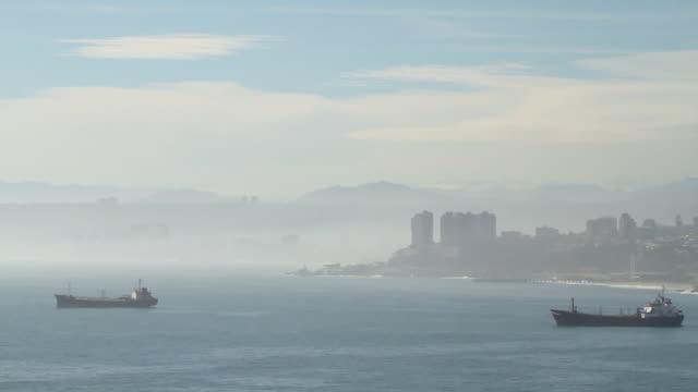 stockvideo's en b-roll-footage met ws pan view of ocean side of valparaiso with fog rolling in and ship in water  / valparaiso, chile  - wiese